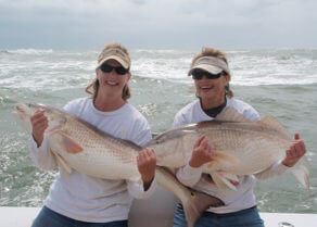 Two ladies holding giant red drum they caught fishing on the Drumrunner.