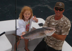 Young lady and first mate on Gecko charter holding out a nice amberjack.